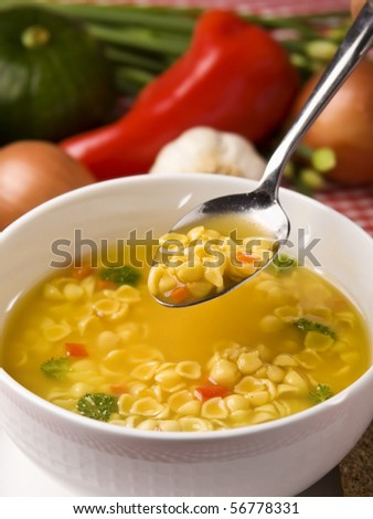 A white bowl full of vegetable and noodle soup with spoon. - stock photo