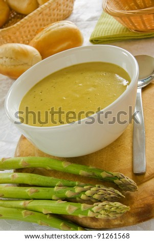 A white bowl of asparagus soup with asparagus spears and bread rolls - stock photo