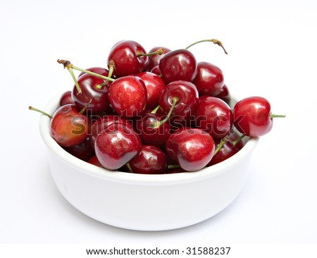 A white bowl of cherries on a white background.