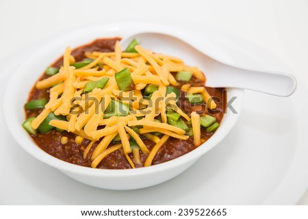 A white bowl of chilli with meat and beans and green poblano chile peppers topped with shredded cheddar cheese - stock photo