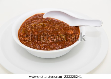 A white bowl of hot, spicy chili with meat and beans - stock photo