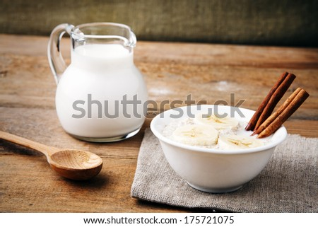 a white bowl of porridge with banana slices and cinnamon sticks, wooden spoon and a milk jug on rustic table  - stock photo