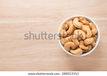 A white bowl with cashew nuts on the table - stock photo