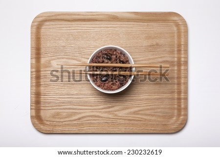 A white bowl with Multi-grain Rice and wood chopsticks on the wood tray isolated white, top view at the studio. - stock photo