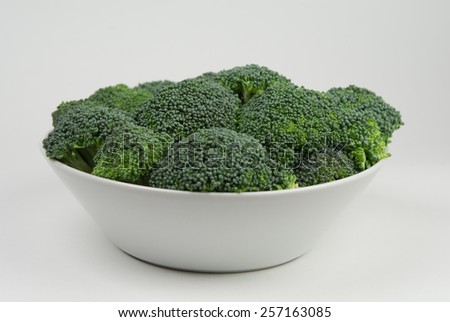 A white bowl with raw fresh broccoli - stock photo