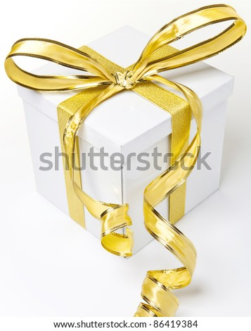 A white box tied with a golden satin ribbon bow. - stock photo
