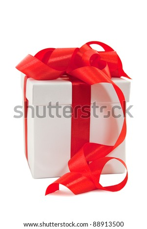 A white box tied with a red satin ribbon bow. A gift for Christmas, Birthday, Wedding, or Valentine's day. Isolated on white with clipping path.