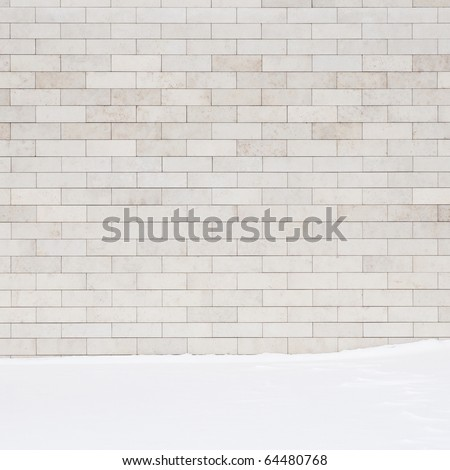 A white brick wall and a ground covered with snow. May use as a background. - stock photo