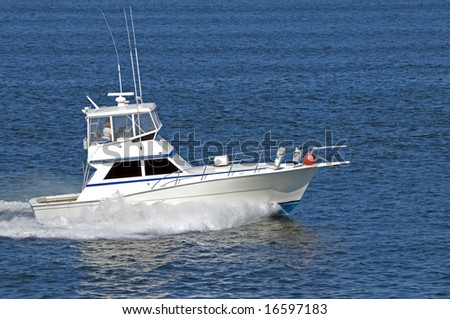 A white cabin cruiser travelling at speed across a calm blue sea. - stock photo