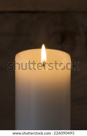 A WHite Candle burning on rustic wooden background - stock photo