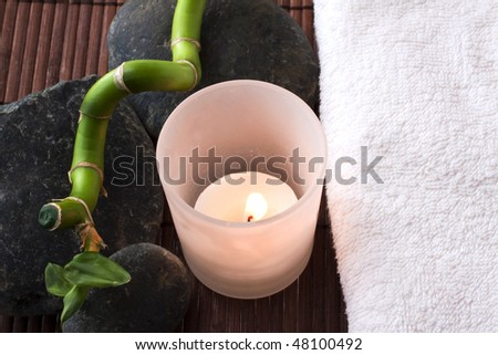 A white candle burns between white towel, bamboo branch and stones