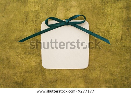 A white card with green bow on a grungy background. - stock photo