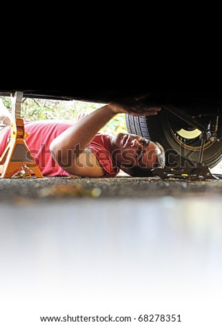 A white Caucasian male mechanic works on an old automobile car.