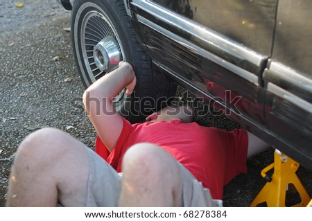 A white Caucasian male mechanic works on an old automobile car. - stock photo