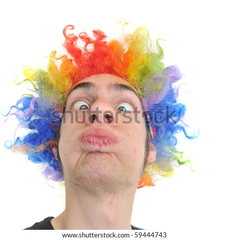 A white Caucasian young adult wearing a silly clown wig with rainbow colorful hair. - stock photo