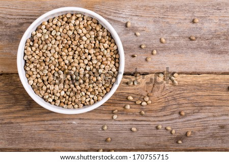 A white ceramic bowl full of hemp seeds over old wood background - stock photo