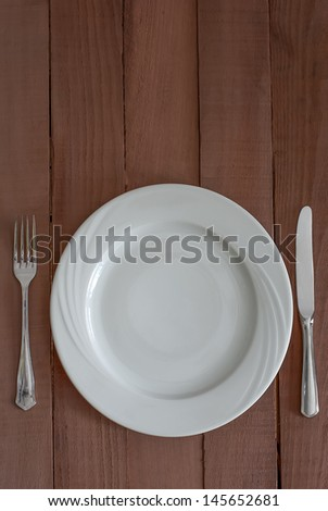 A white china plate with a silver knife and fork on wooden table - stock photo