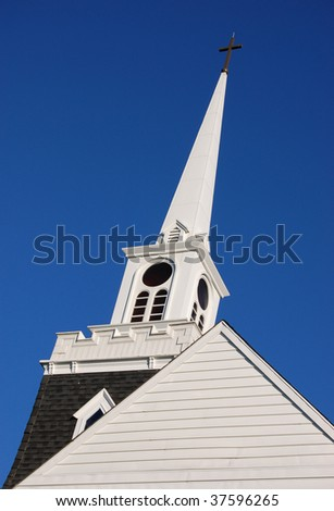 A white Christian steeple against a blue sky