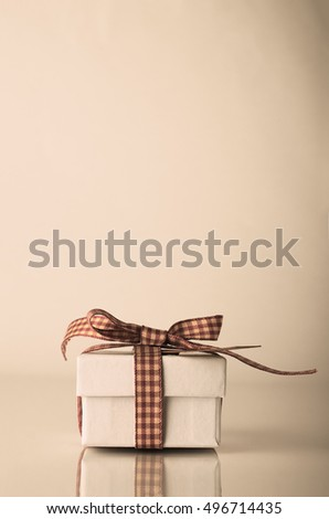 A white Christmas or celebration gift box tied with gingham ribbon on reflective surface.  Hues adjusted for retro or vintage effect.  Copy space above.