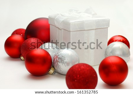 a white christmas present with a bow is sitting in front of an isolated white background, with silver and red sparkling bulb ornaments around it. - stock photo