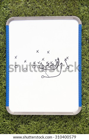 A white clipboard with a football play drawn on it.