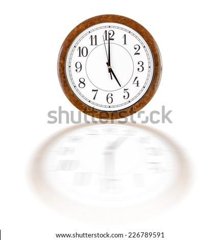 A white clock face in brown wooden frame showing five o'clock over white background with blurry reflection