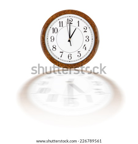 A white clock face in brown wooden frame showing one o'clock over white background with blurry reflection