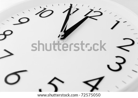 a white clock - five minutes to twelve