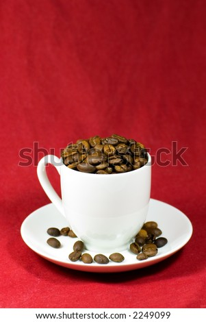 A white coffee cup, overfilled with freshly roasted coffee beans, on a textured red background - stock photo