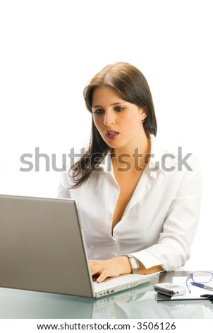 a white collar worker dressing a white shirt sitting at her desk  working with a computer and having an expressive face