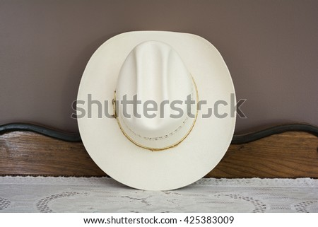 A White Cowboy Hat on an Antique Cabinet Front View - stock photo