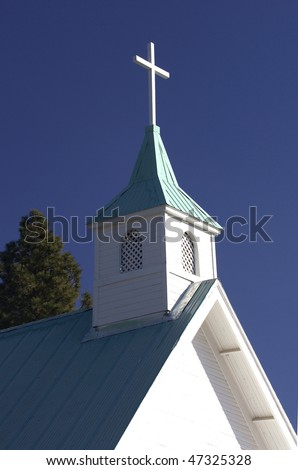 A white cross sits atop the steeple against a bright blue sky.