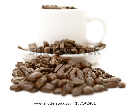 A white cup and bowl with some coffee beans in it. - stock photo