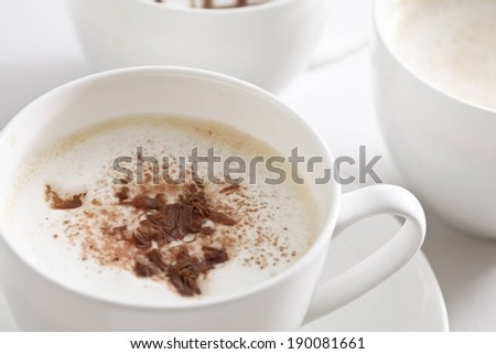 A white cup filled with a hot coffee drink. - stock photo