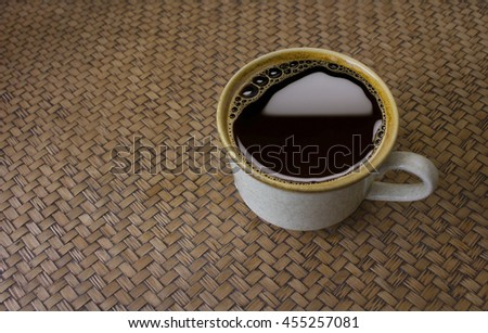 A white cup of black coffee on rustic woven bamboo table - stock photo