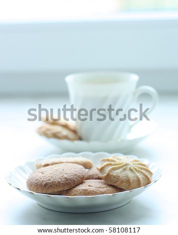 A white cup of cofee or tea with biscuits - stock photo