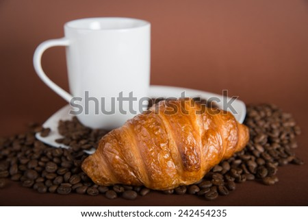 A white cup of coffee with tasty croissants  on brown background.