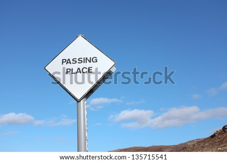 A white diamond shaped road sign with the words 'PASSING PLACE' written in black, against a blue sky with cloud,