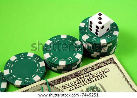 a white die on top of piles of gambling chips and bills of one hundred dollars