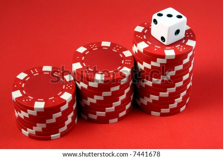 a white die over a three piles of red gambling chips