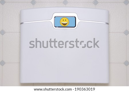 A white, digital bathroom scale displaying a happy face emoji. - stock photo