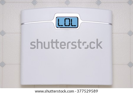 A white digital bathroom scale displaying the text message LOL - stock photo