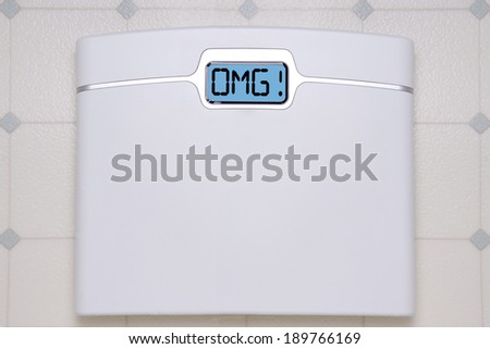 A white digital bathroom scale displaying the text message OMG. - stock photo