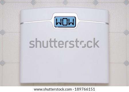 A white digital bathroom scale displaying the text message WOW. - stock photo