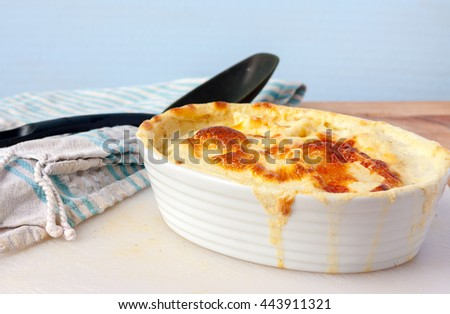 A white dish with freshly cooked dauphinoise potatoes. Which is thin slices of potato slow-cooked in the oven with cream and garlic - stock photo