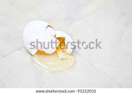 A white egg has hit the vinyl floor of the kitchen and the yolk has spilled out. - stock photo