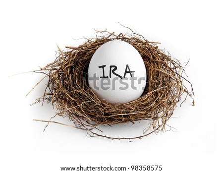 A white egg in a nest on a white background with the word IRA on the egg. - stock photo