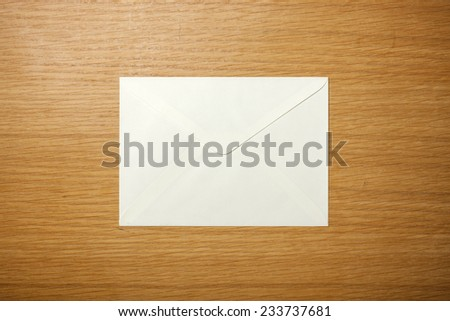 A white envelope on the wooden desk, top view at the studio. - stock photo
