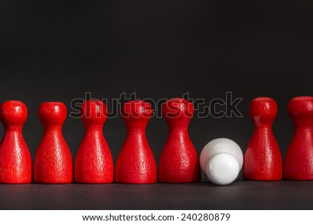 A white fallen game figurine among red ones before black background, concept burnout, failure, death  - stock photo