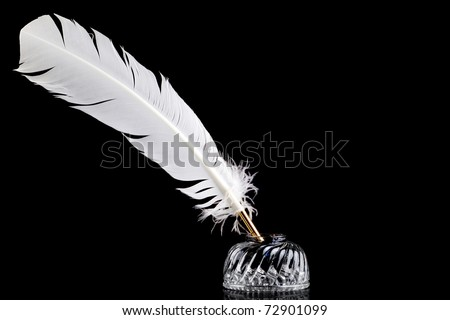 A white feather quill pen and crystal glass ink well isolated on a black background. - stock photo